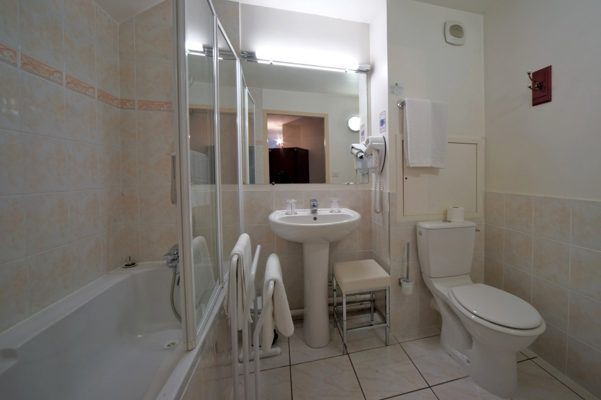 Bathroom with bathtub with transparent separation sink toilettes and hair dryer